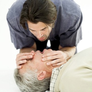Young Man Performing Cpr on an Elderly Man